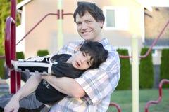 Engendrez le fils handicapé de aide pour jouer à la cour de jeu Photographie stock