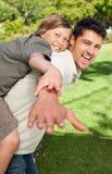 Engendrez le jeu avec son fils en stationnement photographie stock libre de droits