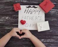 Engendrez le jour du ` s, les mains du ` s de bébé, coeur rouge sur un fond en bois noir Photo stock