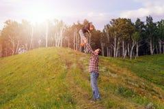 Engendrez le lancement vers le haut de son fils sur le pré photos libres de droits
