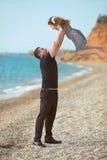 Engendrez le lancer vers le haut de la fille jouant ensemble sur la plage h insouciant Photo stock