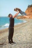 Engendrez le lancer vers le haut de la fille jouant ensemble sur la plage h insouciant Photos stock