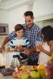 Engendrez le smoothie de portion à ses enfants dans la cuisine Photos stock
