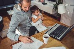 Engendrez le travail à la maison et tenir le fils sur son recouvrement photographie stock