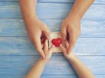 Engendrez les mains papa et enfant de jour du ` s tenant le coeur de boîte-cadeau sur un fond en bois bleu Images stock