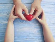 Engendrez les mains papa et enfant de jour du ` s tenant le coeur sur un fond en bois bleu Images libres de droits