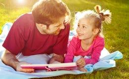 Engendrez lire un livre à sa fille dans le jardin Images stock