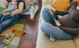 Engendrez lire un livre à son fils tandis que la mère regarde le comprimé images stock