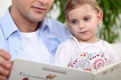 Engendrez la fille de lecture une histoire Images stock