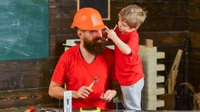 Engendrez, parent avec la barbe dans le fils de enseignement de casque pour utiliser différents outils dans l'atelier d'école Con Photographie stock libre de droits