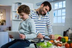 Engendrez parler au téléphone portable tout en coupant les légumes et le fils à l'aide du comprimé numérique Photo stock