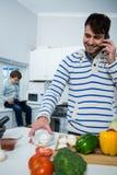 Engendrez parler au téléphone portable tout en travaillant dans la cuisine Image libre de droits