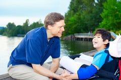 Engendrez parler avec le fils handicapé dans le fauteuil roulant au lac Photos libres de droits
