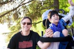 Engendrez parler avec le fils handicapé dans le fauteuil roulant au lac Image libre de droits