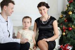 Engendrez, petite fille et la mère de sourire s'asseyent sur le sofa Photos libres de droits