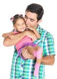 Engendrez porter et embrasser sa petite fille multiraciale drôle Image libre de droits