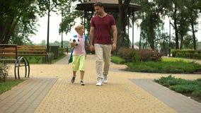 Engendrez porter le fils aux classes de sport, garçon tenant la boule et parlant avec le papa clips vidéos