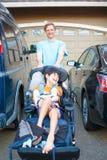 Engendrez pousser le fils handicapé dans le fauteuil roulant après des voitures dans l'allée Images libres de droits