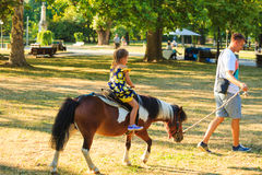 Engendrez prennent son peu de dother pour un tour sur le cheval de poney en parc Photo libre de droits