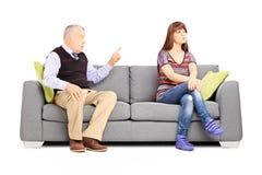 Engendrez reprimending sa fille indifférente assise sur un divan Images libres de droits
