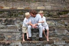 Engendrez Sitting avec ses deux jeunes fils dehors Images stock