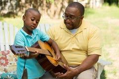 Engendrez teaaching son son fils pour jouer la guitare Images stock
