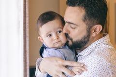 Engendrez tenir et embrasser son bébé garçon avec affection Images libres de droits