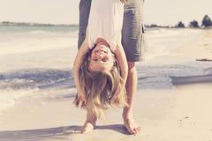 Engendrez tenir la jeune et belle petite fille blonde douce par ses pieds jouant en ayant l'amusement sur la plage dans l'amour d Image libre de droits