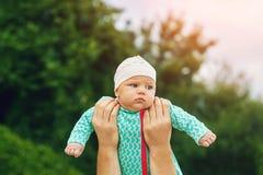 Engendrez tenir le bébé à la longueur du ` s de bras Image libre de droits