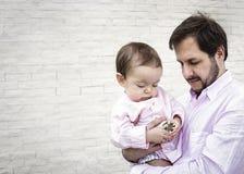 Engendrez tenir le fils de bébé garçon à un mur de briques blanc vide Images stock