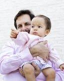 Engendrez tenir le fils de bébé garçon à un mur de briques blanc vide Photos libres de droits