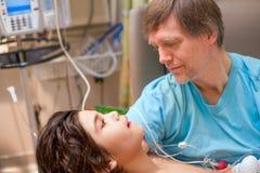Engendrez tenir le fils malade handicapé sur le recouvrement dans l'hôpital Photographie stock libre de droits
