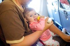 Engendrez tenir sa fille de bébé pendant le vol sur l'avion partant en vacances Images stock