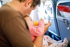 Engendrez tenir sa fille de bébé pendant le vol sur l'avion partant en vacances Photos stock