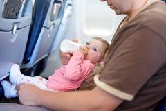 Engendrez tenir sa fille de bébé pendant le vol sur l'avion partant en vacances Photographie stock libre de droits