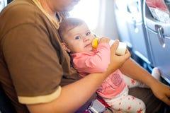 Engendrez tenir sa fille de bébé pendant le vol sur l'avion partant en vacances Images libres de droits