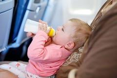 Engendrez tenir sa fille de bébé pendant le vol sur l'avion partant en vacances Image stock