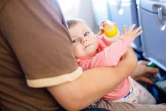 Engendrez tenir sa fille de bébé pendant le vol sur l'avion partant en vacances Image libre de droits