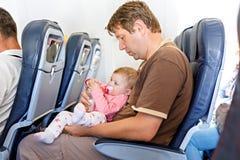 Engendrez tenir sa fille de bébé pendant le vol sur l'avion partant en vacances Photo stock