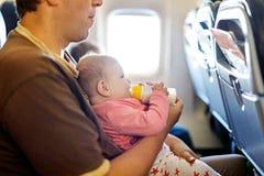 Engendrez tenir sa fille de bébé pendant le vol sur l'avion partant en vacances Photographie stock