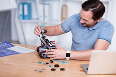 Engeneer in blue t-shirts constructing droid. Work is fun. Smiling man in his forties in the process of making a little robot Royalty Free Stock Image