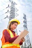Engenharia da mulher que trabalha na torre de alta tensão Fotografia de Stock