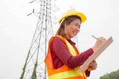 Engenharia da mulher que trabalha na torre de alta tensão Fotografia de Stock Royalty Free