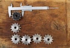 A engenharia utiliza ferramentas as engrenagens e o compasso de calibre na tabela de madeira Esfera 3d diferente Foto de Stock Royalty Free