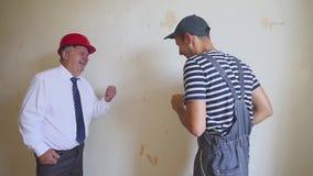 Engenheiro chefe e um trabalhador novo que tem o divertimento e que dança em um canteiro de obras Sucesso na construção video estoque