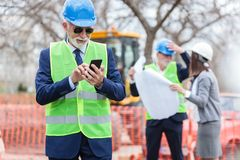Engenheiro chefe ou homem de negócios feliz que usa seu telefone esperto ao inspecionar um canteiro de obras imagem de stock royalty free