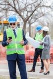 Engenheiro chefe ou homem de negócios sério que usa seu telefone esperto ao inspecionar um canteiro de obras Dois pessoas que olh imagens de stock