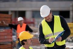 Engenheiro civil que dá instruções ao trabalhador da construção foto de stock royalty free