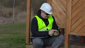 Engenheiro civil que usa o PC da tabuleta na estrutura de madeira da construção filme