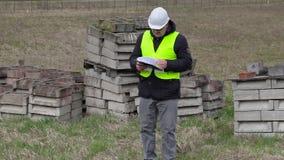 Engenheiro civil que verifica originais no lugar onde canteiro de obras novas video estoque